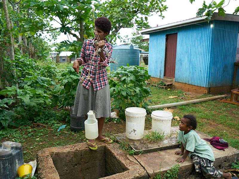 Water is fetched from an unprotected well using a bucket. Soko boils the water over a fire to kill off some of the bacteria, however there is no guarantee that it's safe for drinking.
