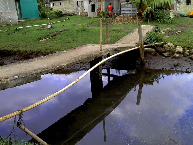 Nacomoto village pipe crossing a concrete foot bridge